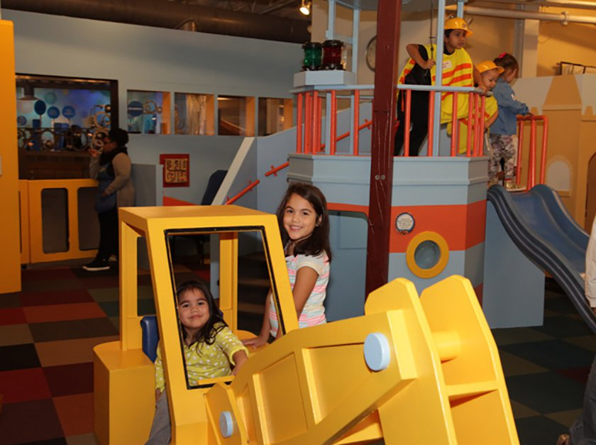 Two girls playing inside a child-sized wooden digger.