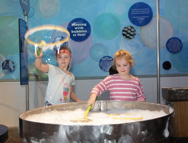 Two girls using bubbles wands to make bubbles.