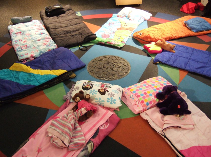 Sleeping bags and stuffed animals in a circle in a Museum exhibit