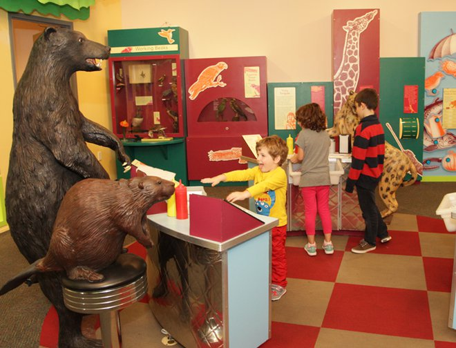 Three children exploring the Feasts for Beasts exhibit.