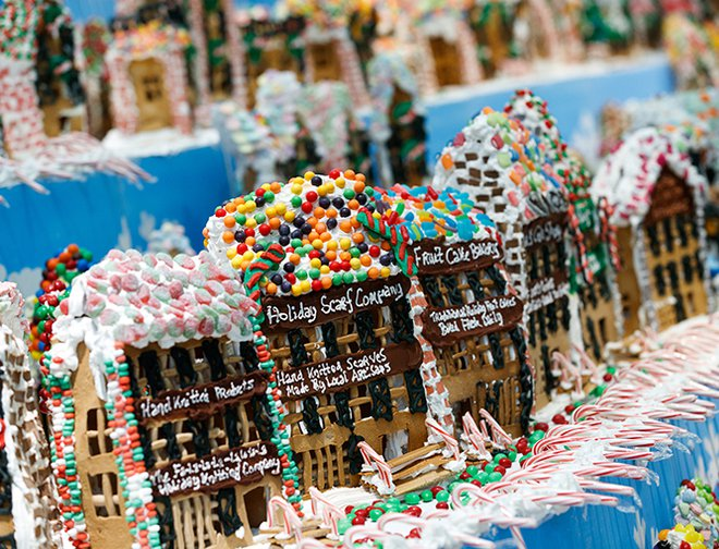 Rows of gingerbread houses decorated with white frosting and a variety of candy.