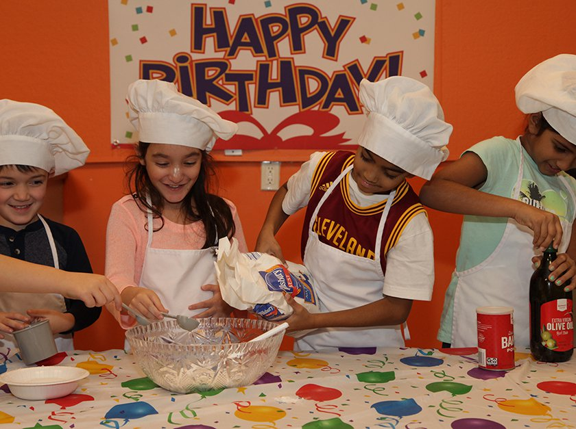 Children mix together ingredients for recipe during Kids in the Kitchen birthday party