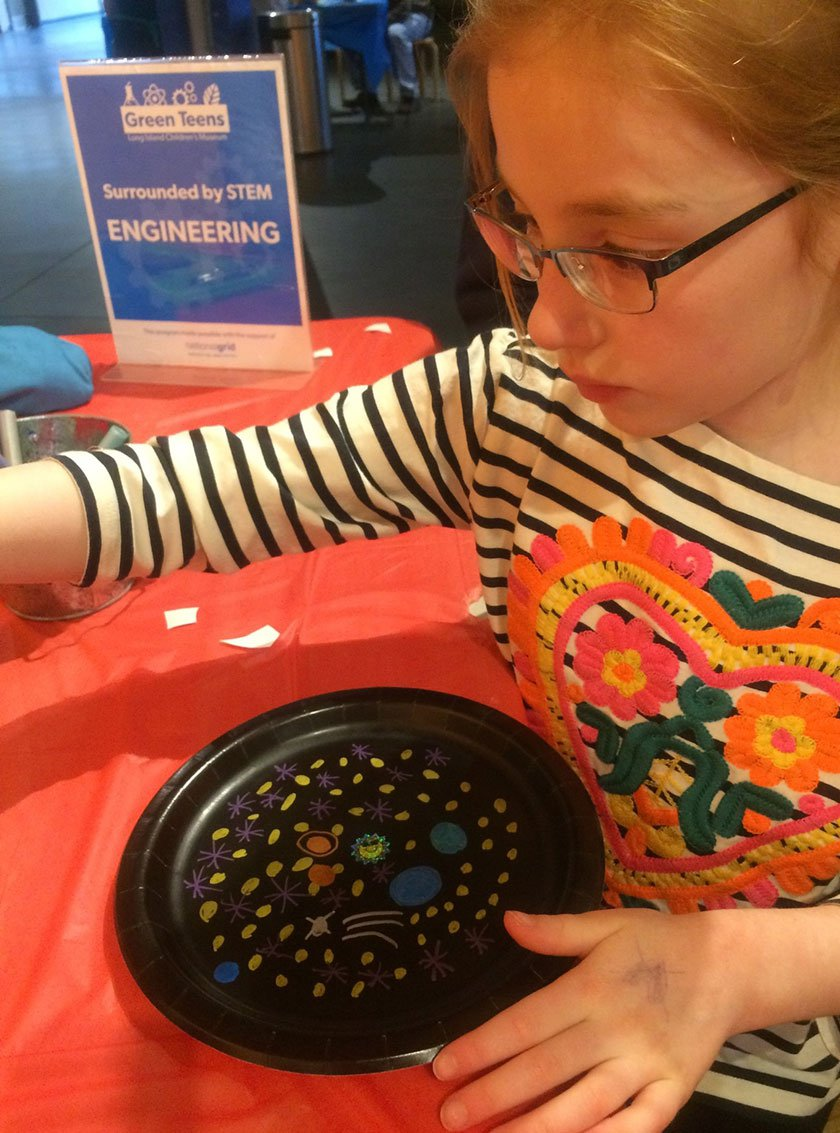 A young visitor creating a galaxy using metallic pens on a black paper plate.