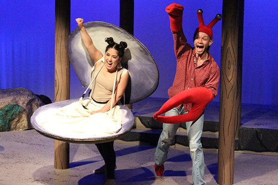 Two cast members on stage dressed as a clam and as a red crab.