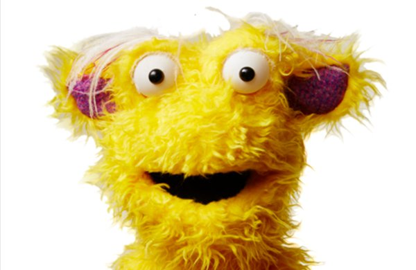 A fuzzy yellow puppet troll with his mouth open. Gruff has pink ears, big white eyes, and white hair on his head.