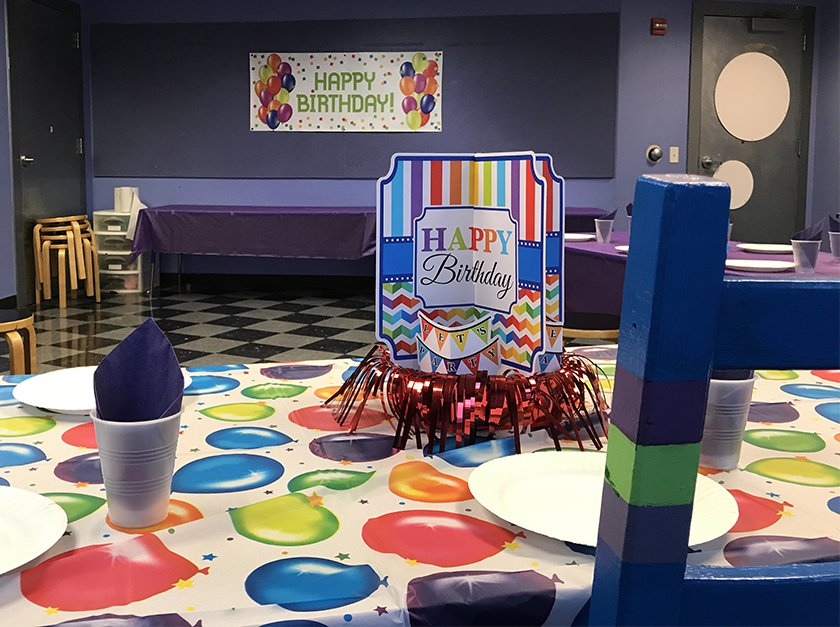 Museum studio with purple walls set up with party decorations and Happy Birthday banner on wall.