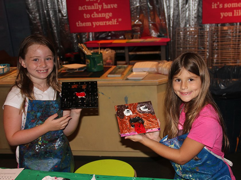 Two girls in paint-filled smocks showing off their paintings.