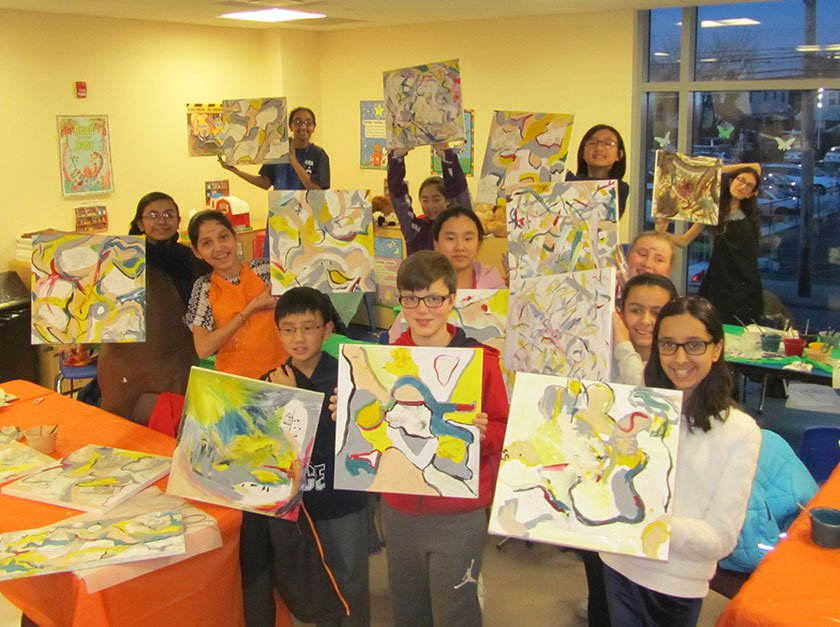 A group of adolescents holding up their DeKooning artwork in a classroom.