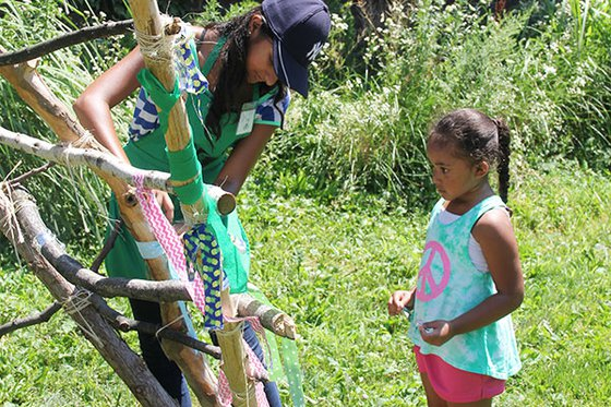 A Museum volunteer helping a young visitor tie a ribbon on our hand-made stick tent.