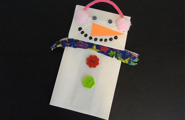 A white paper bag decorated with a face and a scarf to look like a snow person.