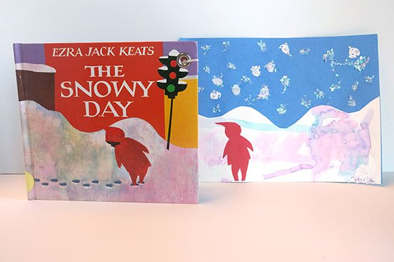 "The book ""The Snowy Day"" with a hand crafted picture. The picture has a blue background, snow on the ground and falling from the sky, with a child dressed in a red coat and red hat."
