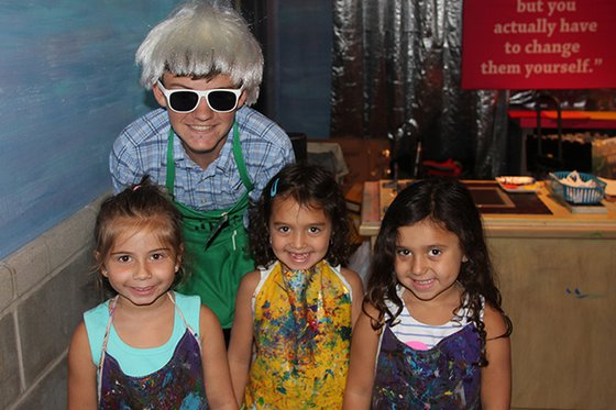 A Museum volunteer wearing a Andy Warhol wig standing with children.