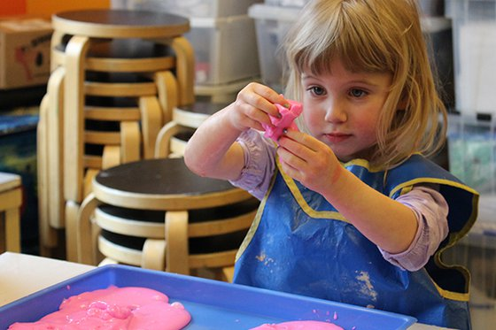 young girl playing with oobleck at workshop table
