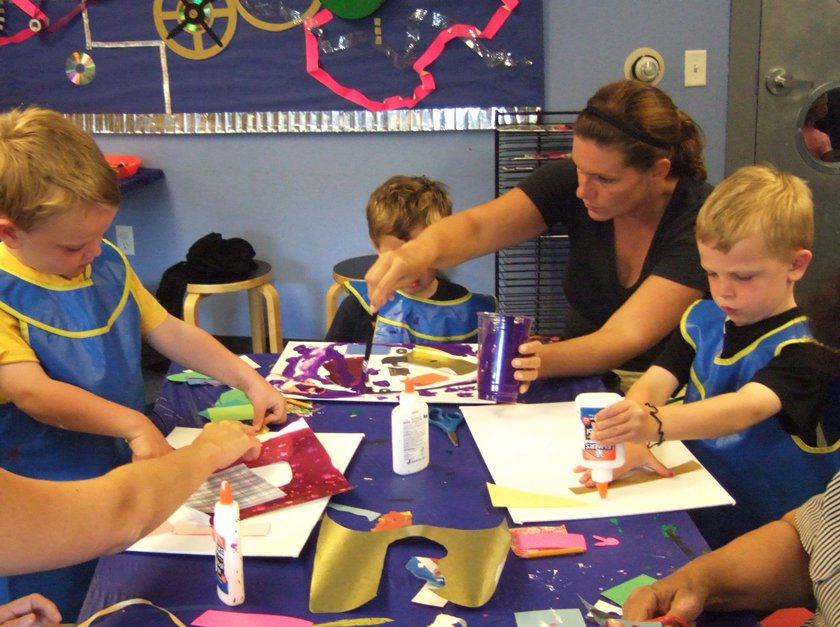 Adult and children complete a craft in Museum.