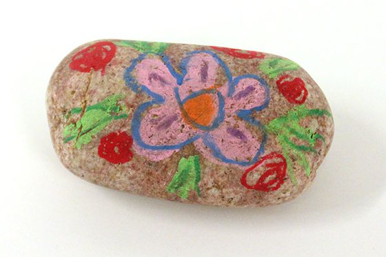 A stone decorated with a drawing of a flower.