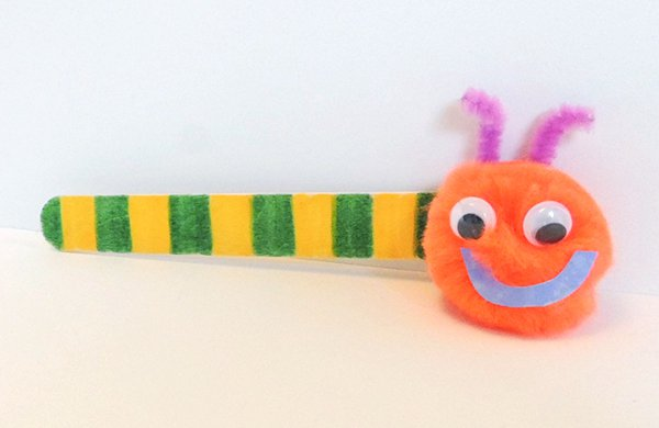 A yellow and green popsicle with a pompom attached to one end. The pompom has googley eyes and a paper smile to resemble a bug.