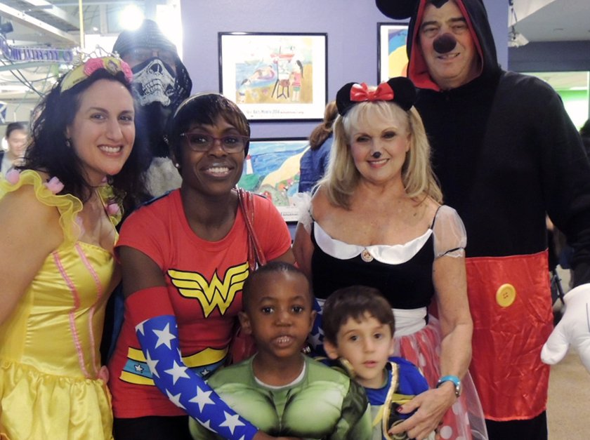 Children and adults posing for picture in Halloweeen costumes.