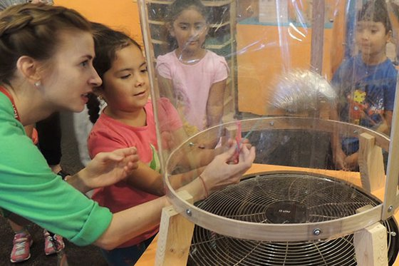 Museum educator assisting children with wind tunnel.