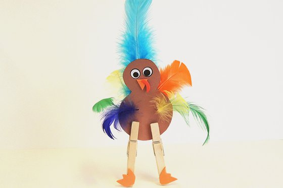 A paper turkey with colorful feathers and clothespin legs.