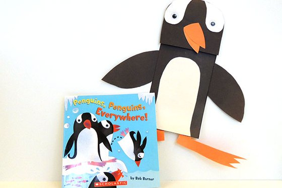 "The book ""Penguins, Penguins, Everywhere!"" with a paper penguin puppet."