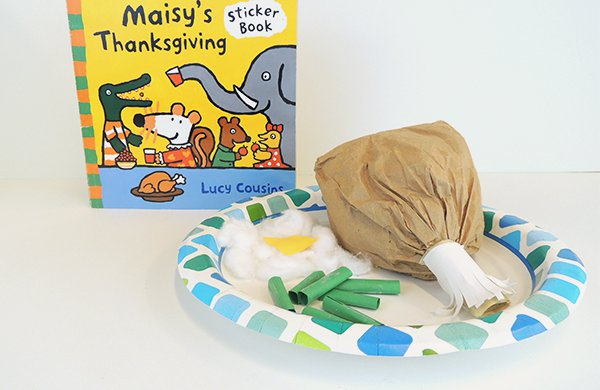 "The book ""Maisy's Thanksgiving"" with a plate with a paper turkey drumstick, paper mashed potatoes, and paper stringbeans."