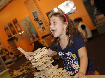 A girl excitedly playing with KEVA blanks and building a structure.