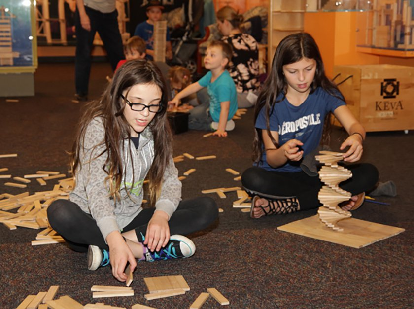 Two pre-teen visitors sitting next to each other building a structure using KEVA planks.