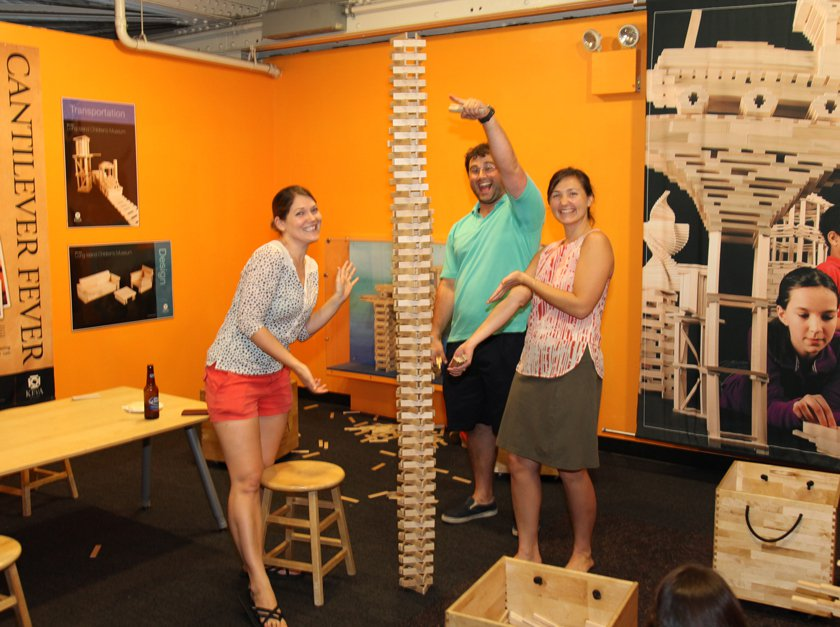 Three adults playing with KEVA planks during an evening at the Museum